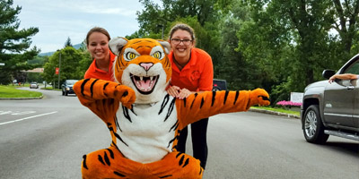 Two students pose with Coby T Tiger mascot
