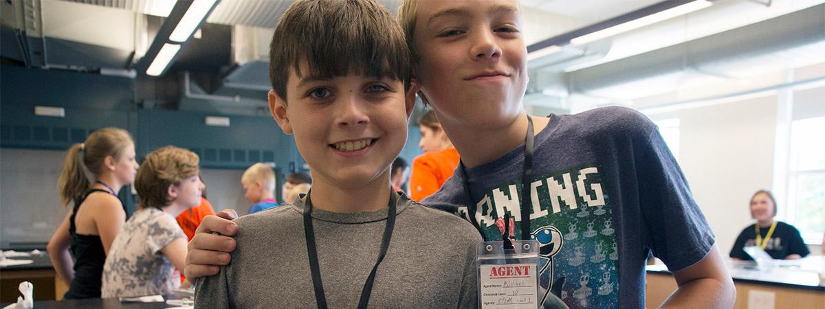 two elementary kids smile in the biotech lab