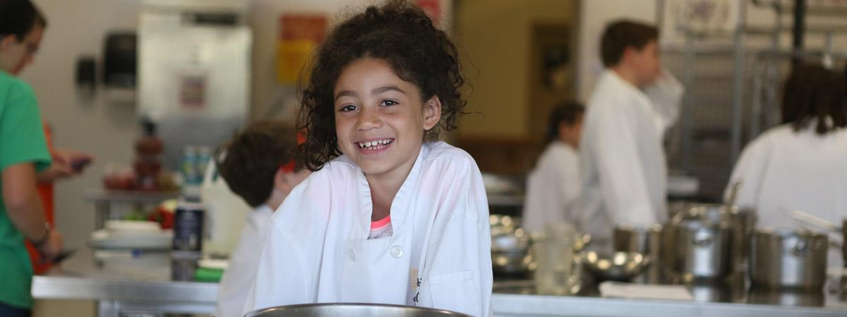 young girl smiling in the culinary lab