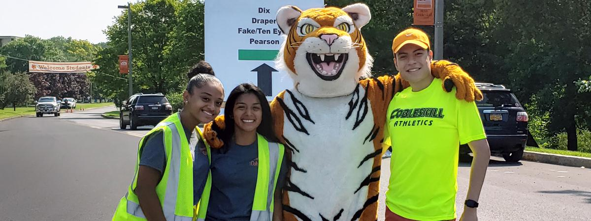 students smile with tiger mascot at the entrance to campus