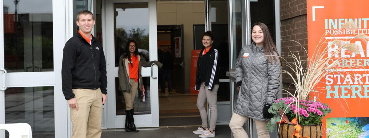 students hold doors open for guests