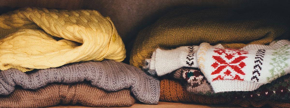 sweaters on wooden shelf