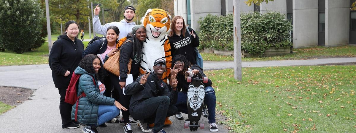 students posing with Coby the Tiger