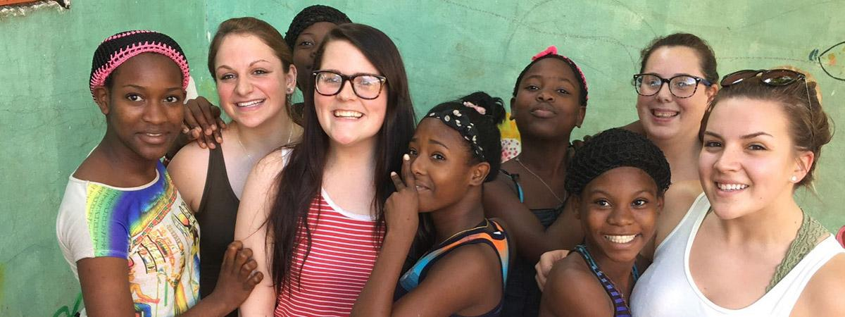 group of smiling students pose with local kids in the Dominican Republic