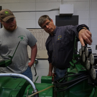 student and teacher working on a tractor