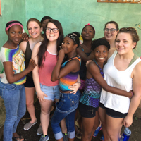 students pose with younger children on a trip to Haiti