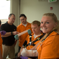 students practicing first-aid on a volunteer