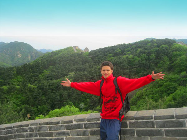 Pedro Gonzalez stands on the Great Wall of China during his summer service learning program.